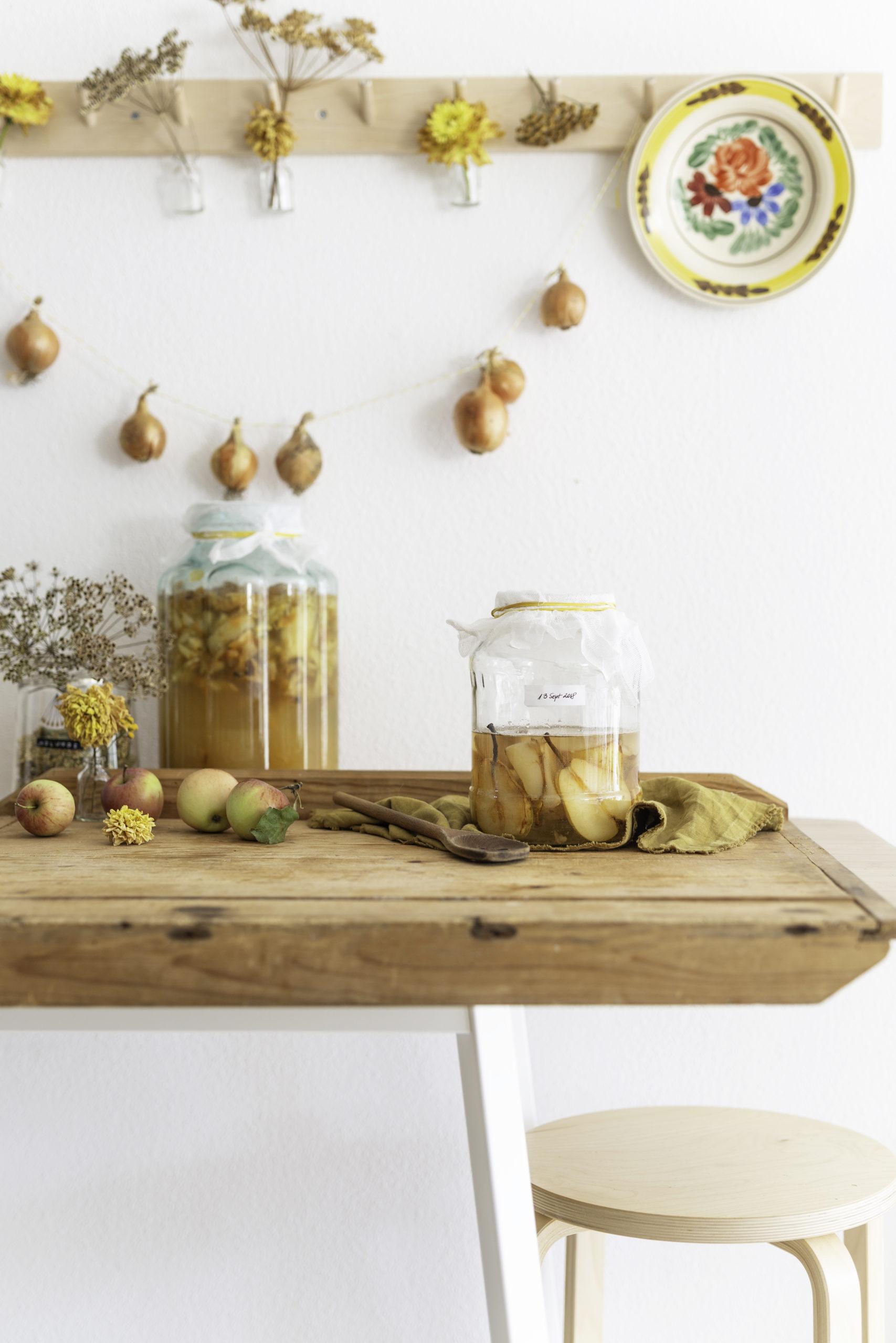 Apfelessig selber machen - Einfaches Rezept (Teil 1) - Lose Äpfel und Essigglas auf einem Holztisch vor weißer Wand mit Blumen und Zwiebel-Girlande | Syl Gervais - Vegane Rezepte