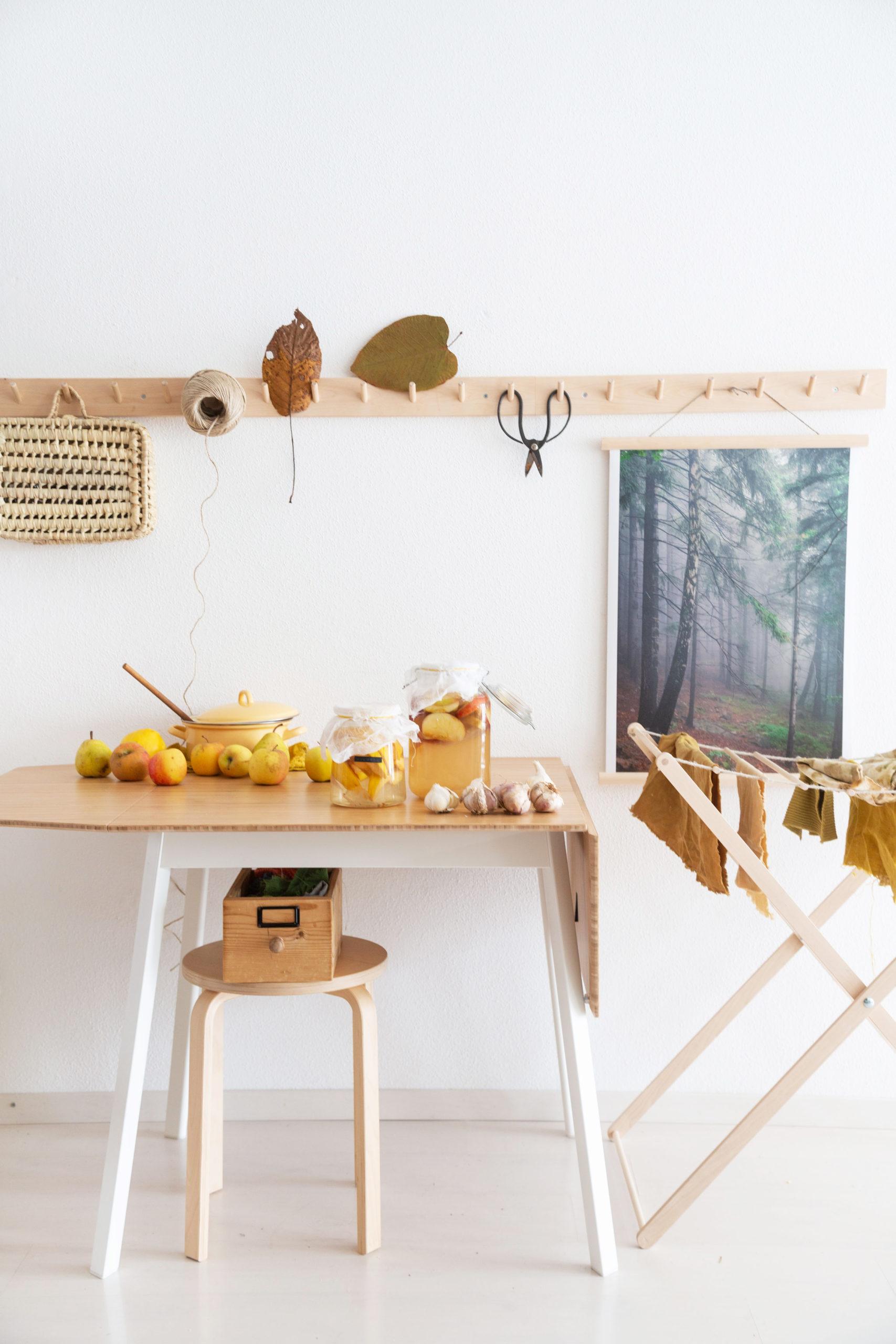 Apfelessig selber machen - Einfaches Rezept (Teil 1) - Essiggläser auf Holztisch vor weißer Wand mit Holz-Hakenleiste und Herbst-Deko | Syl Gervais - Vegane Rezepte